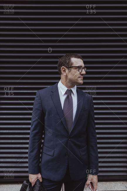 Businessman with smart phone holding bag while looking away in city