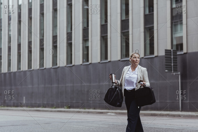 Female entrepreneur with bag and coffee cup looking away in city