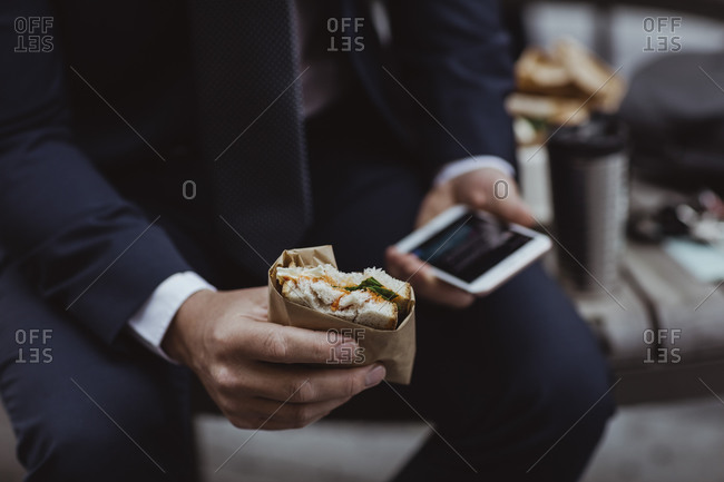 Midsection of entrepreneur with smart phone and sandwich sitting in city