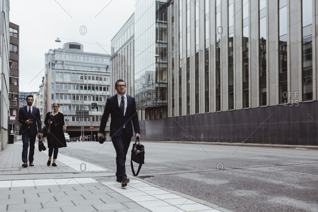 Male entrepreneur with bag walking ahead of coworkers in city