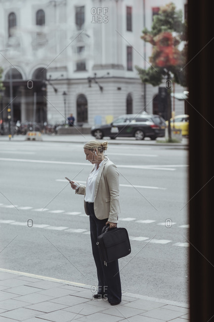 Side view of entrepreneur with bag using mobile phone while standing in city