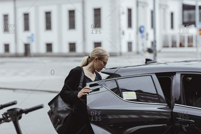 Businesswoman with bag sitting in car