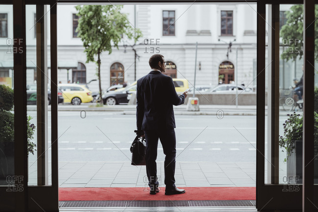 Full length of businessman with bag looking away in city