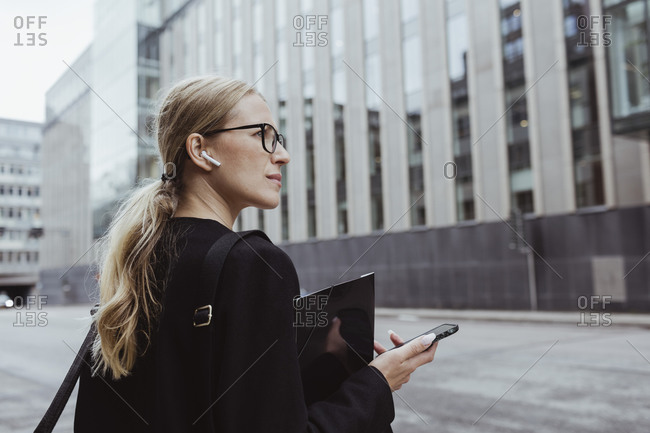 Rear view of businesswoman with in-ear headphones holding file in city