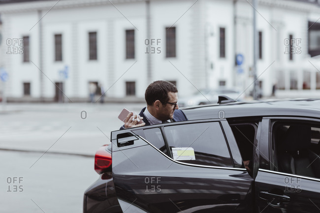 Businessman with smart phone getting in to a taxi