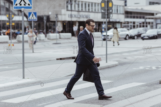 Businessman with bag crossing road in city