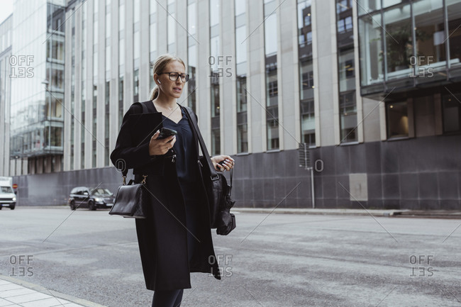 Contemplating businesswoman with smart phone walking in city