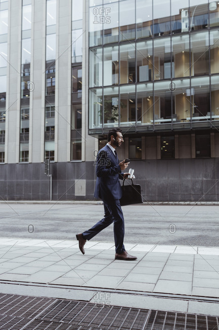 Entrepreneur with bag using smart phone while walking in city