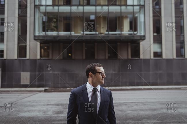 Businessman wearing eyeglasses while looking away in city
