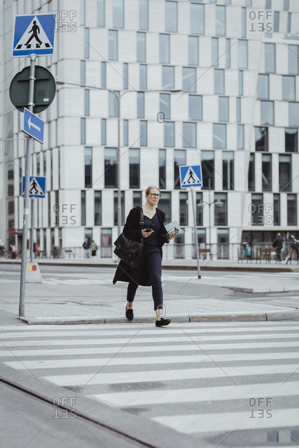 Full length of businesswoman with smart phone crossing road in city