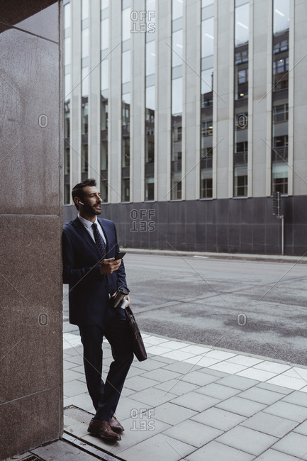 Entrepreneur with bag holding smart phone while standing in city
