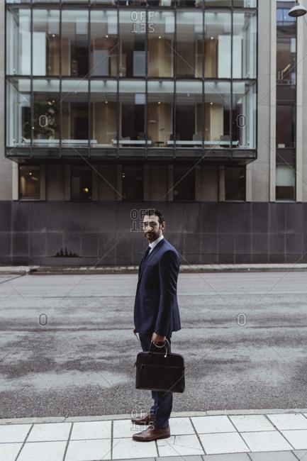 Full length portrait of male entrepreneur with bag standing in city