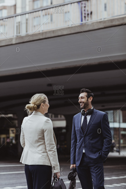 Smiling entrepreneur with bag talking to female coworker while standing in city