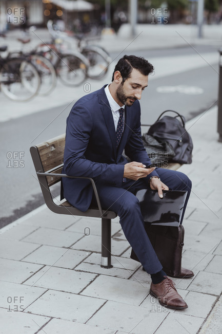 Entrepreneur with bag and file using smart phone while sitting on bench in city