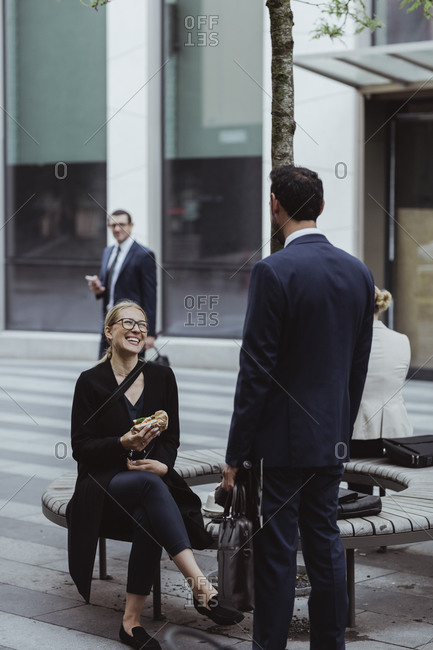 Smiling female entrepreneur with sandwich talking to coworker while sitting in city