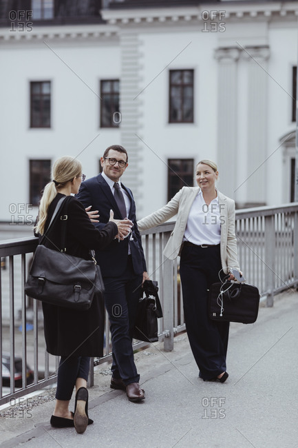 Smiling male and female entrepreneurs talking while standing by railing in city