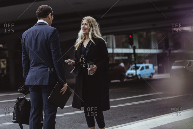 Smiling businesswoman with coffee cup talking to coworker while standing in city