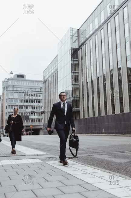 Male entrepreneur with bag walking ahead of female coworker in city