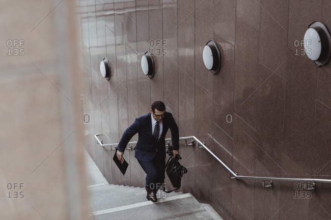 Businessman with bag climbing staircase in city