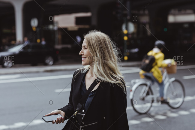 Smiling businesswoman with smart phone looking away in city