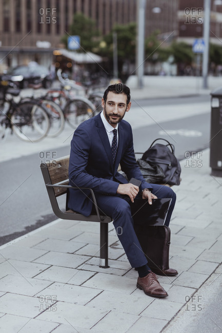 Entrepreneur with bag and file looking away while sitting on bench in city