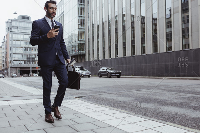 Male entrepreneur with bag using smart phone while walking in city