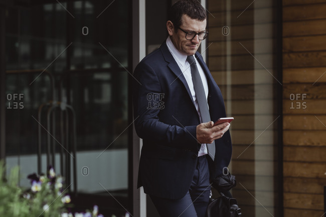 Entrepreneur using smart phone while walking in city
