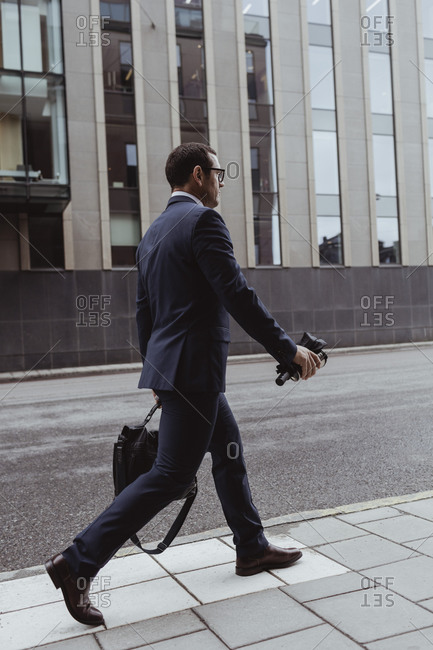 Side view of businessman with bag walking on sidewalk in city