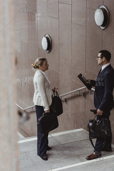 Male entrepreneur talking to female colleague on steps in city