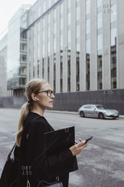 Side view of businesswoman with in-ear headphones holding file in city