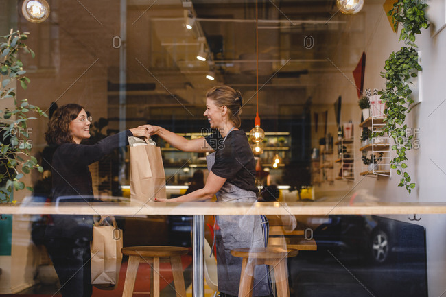 Side view of smiling saleswoman giving shopping bag to female customer at checkout counter seen through glass window