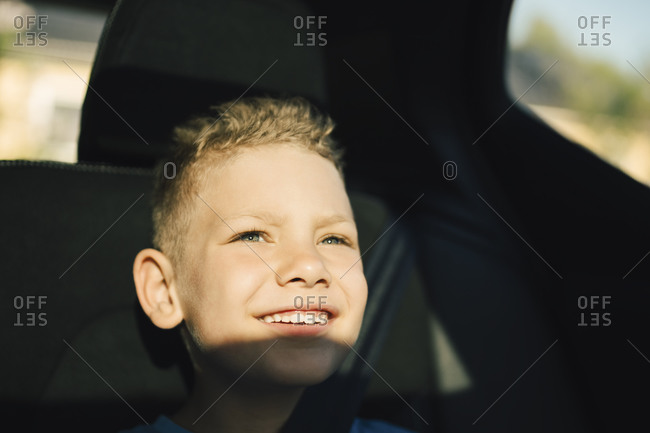 Smiling boy with seat belt looking away while sitting in car