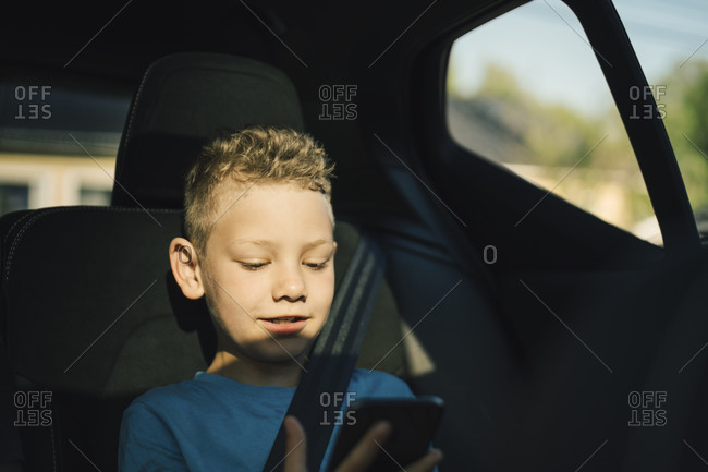 Smiling boy with seat belt using smart phone in car