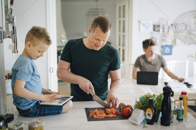 Father cutting tomato while son using digital tablet on kitchen counter