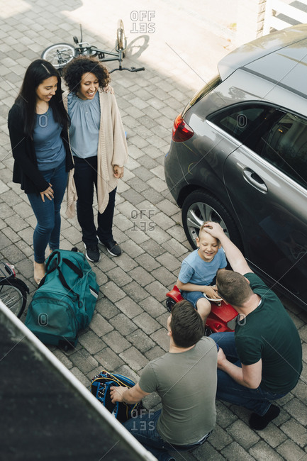 Fathers embracing son while lesbian couple standing by car during weekend