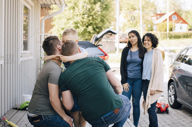 Fathers embracing son while lesbian couple standing outdoors during weekend