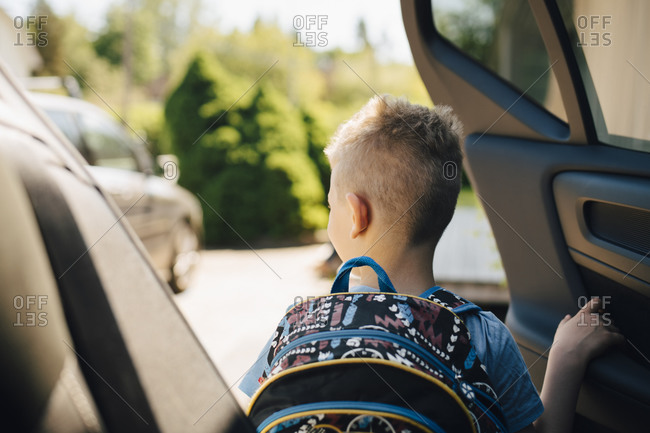 Rear view of boy with backpack opening car during sunny day