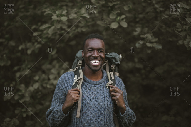 Smiling man with backpack standing in forest