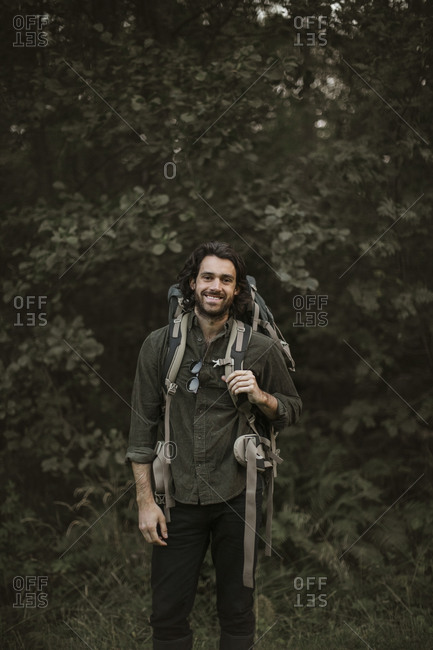 Portrait of smiling man with backpack in forest
