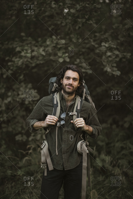 Portrait of man with backpack in forest