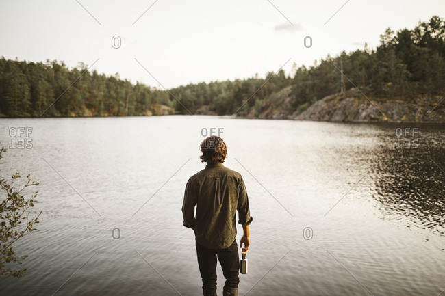 Rear view of man standing by lake in forest during vacation
