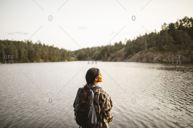 Rear view of woman with backpack standing against lake in forest