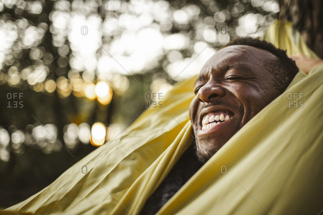 Cheerful man lying over hammock in forest
