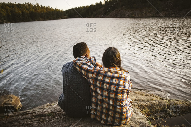 Rear view of man and woman sitting by lake in forest