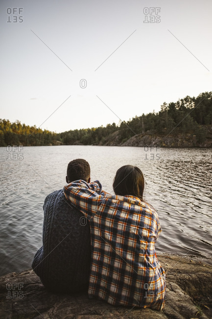 Rear view of man and woman sitting against lake in forest