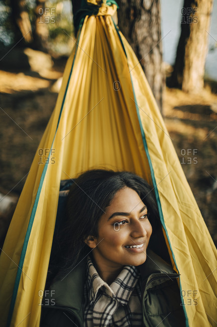 Smiling woman looking away on hammock in forest during vacation