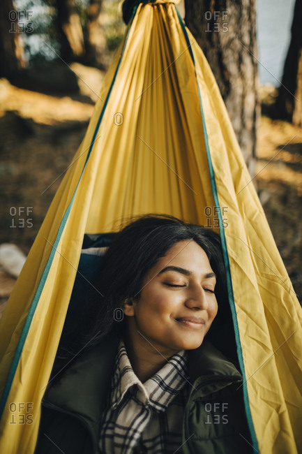 Smiling woman with closed eyes on hammock in forest during vacation