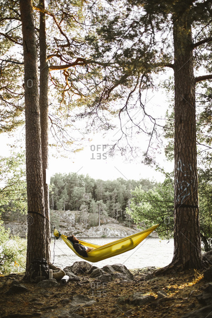 Young man sleeping in hammock in forest