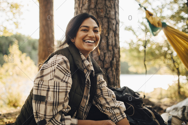 Portrait of smiling woman in forest during vacation