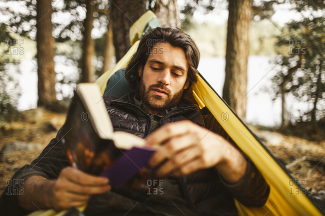Young man enjoying reading book while lying on hammock in forest